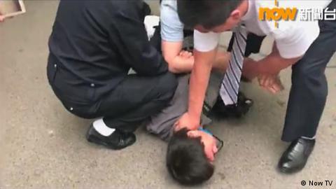 香港攝影記者徐駿銘北京採訪期間被警員強行壓倒在地 (Now TV截圖)