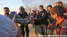 Palestinians carry away a protester injured during clashes with Israeli forces along the border east of Khan Yunis in the southern Gaza Strip on May 15, 2018 after demonstrations marking 70th anniversary of Nakba -- also known as Day of the Catastrophe in 1948 -- and against the US' relocation of its embassy from Tel Aviv to Jerusalem. (Photo by SAID KHATIB / AFP) (Photo credit should read SAID KHATIB/AFP/Getty Images)