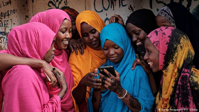 Young Somali refugee women look at a smartphone as they stand together at Dadaab refugee complex
