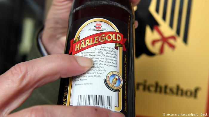A finger points to the word bekoemmlich on a beer bottle (picture-alliance/dpa/U. Deck)