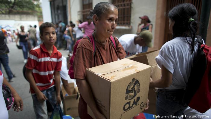 A Venezuelan woman carries a box of goverment subsidized food.