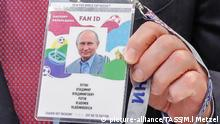 Vladimir Putin holds up his Fan ID (picture-alliance/TASS/M.l Metzel)