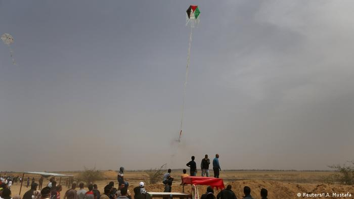 Palestinians set a kite alight to fly into Israel