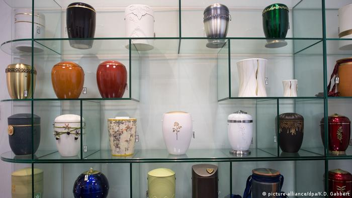 Urns on shelves in a funeral home (picture-alliance/dpa/K.D. Gabbert)