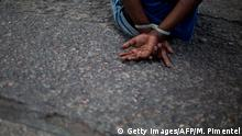 07.02.2018 *** TOPSHOT - A suspect remains handcuffed after being arrested by Rio's Civil Police during a joint operation at Cidade de Deus (City of God) favela, in Rio de Janeiro, Brazil, on February 07, 2018. More than 3,000 soldiers deployed on Wednesday to provide backup to Rio's police during an operation at Cidade de Deus favela in the violent western zone of the city, to search and arrest suspects related to drug trafficking activities, official sources said. / AFP PHOTO / MAURO PIMENTEL (Photo credit should read MAURO PIMENTEL/AFP/Getty Images)
