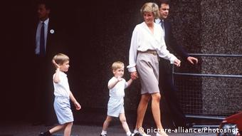 William and Harry as very young boys, with Diana holding Harry's hand.