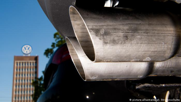The exhaust pipe of a car with a VW high-rise building in the background