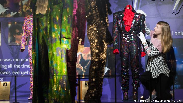 A woman looks at Prince's suits (picture-alliance/Zumapress/R. Tang)