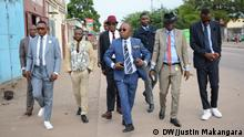 """S.A.P.E. is an acronym for """"Société des Ambianceurs et des Personnes Élégantes"""" (Society of Ambiance-Makers and Elegant People). Sometimes referred to as the """"dandies from the slums"""" by foreign media, they want to be more than an African fashion movement. The subculture he is part of started in colonial times with Congolese men imitating and exaggerating the style of the white bourgeoisie from Paris. Today, there are thousands of Sapeurs, not only in Africa but also in Congolese quarters of Paris, London and Brussels. Im Bild: Baniakina Cyr Ericson, insurance manager, 25 years old in SAPE and father of 2 children, with these supporters"""