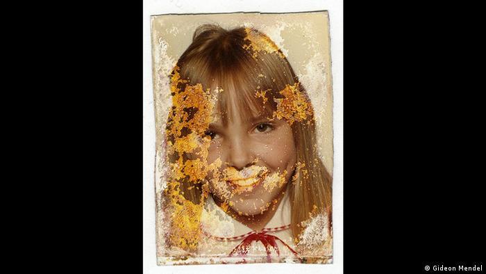 Passfoto eines jungen Mädchens, das in die Kamera lächelt. Das Foto ist durch Wasser beschädigt und fleckig. Aus der Forum Frankfurt Ausstellung EXTREME. ENVIRONMENTS. (Gideon Mendel)