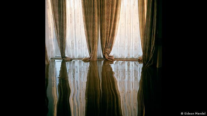 Fotografie eines großen Fensters mit Vorhängen, die sich im Wasser spiegeln. Zu sehen in der Forum Frankfurt Ausstellung EXTREME. ENVIRONMENTS. (Gideon Mendel)