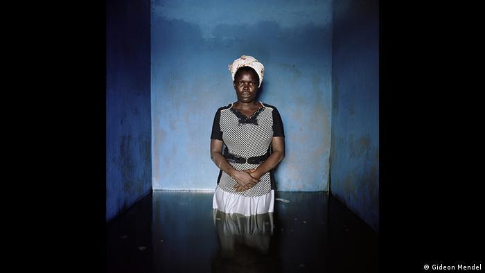 Fotografie einer afrikanischen Frau, die in einem blau gestrichenen Raum bis zu den Oberschenkeln im Wasser steht. Aus der Forum Frankfurt Ausstellung EXTREME. ENVIRONMENTS. (Gideon Mendel)