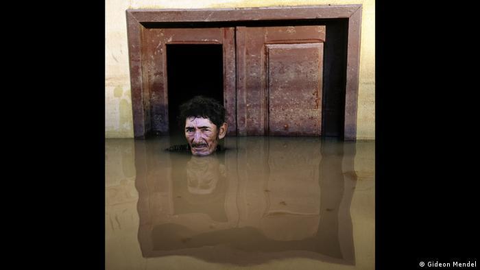 Fotografie eines Mannes, der bis zum Kopf in trübem Wasser vor einer Haustür steht. Aus der Forum Frankfurt Ausstellung EXTREME. ENVIRONMENTS. (Gideon Mendel)