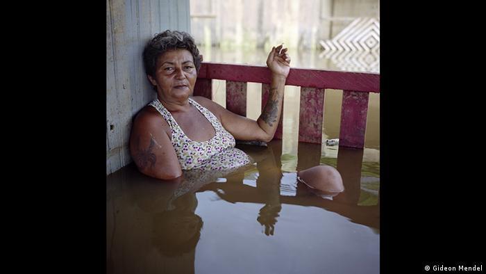Fotografie einer älteren Frau, die, an eine Hauswand gelehnt, im Wasser sitzt, die Beine überschlagen, eine Zigarette rauchend. Zu sehen in der Forum Frankfurt Ausstellung EXTREME. ENVIRONMENTS. (Gideon Mendel)