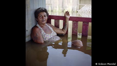 Photograph of an elderly woman leaning against a house wall on a balcony, sitting in deep water while smoking a cigarette (Gideon Mendel)