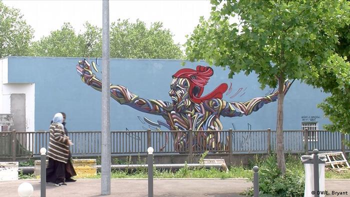 Two women walking past graffiti in Grigny