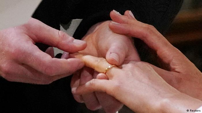 Prince Harry puts the ring on Meghan's left ring finger (Reuters)