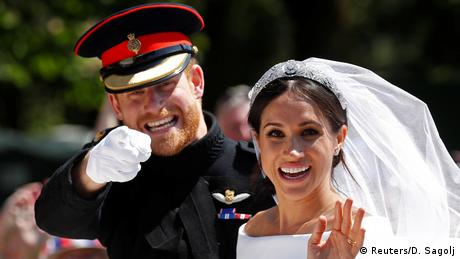 Britain's Prince Harry gestures next to his wife Meghan as they ride a horse-drawn carriage after their wedding ceremony at St George's Chapel in Windsor Castle