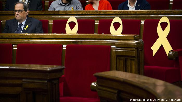 Quim Torra sits next to three empty seats in parliament