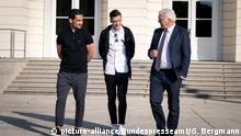Ilkay Gundogan und Mesut Özil speak with Frank-Walter Steinmeier in front of Schloss Bellvue in Berlin