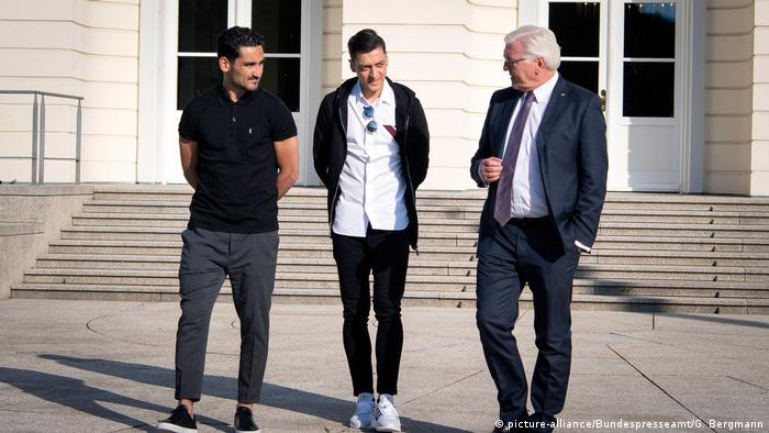 Ilkay Gundogan und Mesut Özil speak with Frank-Walter Steinmeier in front of Schloss Bellvue in Berlin
