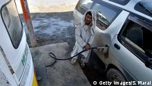 An Afghan fuel station employee fills the tank of a car at a service station in Kabul, 17 April 2006. Oil prices hit 70 USD a barrel in Asian trade on concerns over tight US gasoline stocks and continued fears the United States could launch military strikes against Iran's nuclear facilities, dealers said. AFP PHOTO/ SHAH Marai (Photo credit should read SHAH MARAI/AFP/GettyImages)