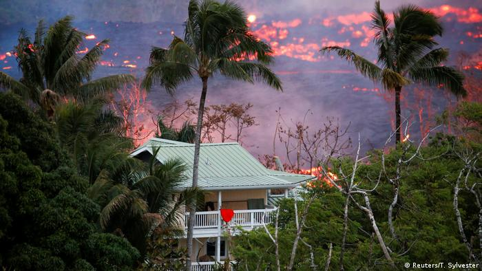 Flow of lava seen behind a house in Hawai (Reuters/T. Sylvester)