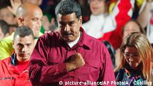 20.05.2018 Venezuela's President Nicolas Maduro places his fist against his heart as he arrives with his wife Cilia Flores to address supporters from the presidential palace after the National Electoral Council said he was re-elected in a vote marred by opposition boycott in Caracas, Venezuela, Sunday, May 20, 2018. (AP Photo/Ariana Cubillos)