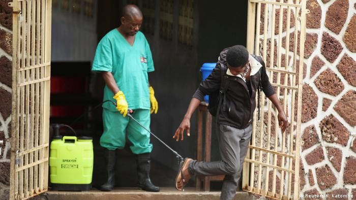 A health worker sprays a visitor with chlorine at a hospital preparing to receive suspected Ebola cases in the Democratic Republic of Congo