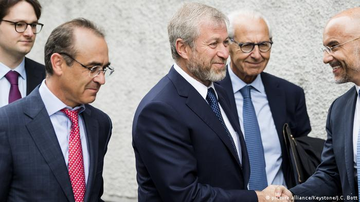 Russian oligarch Roman Abramovich, center, arrives with his team of lawyers before a hearing, at the District Court of Sarine in Fribourg