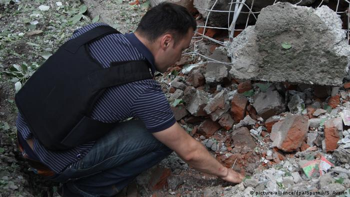 Representatives of the Gorlovka monitor group collect shell fragments in the village of Gorlovka, Donetsk