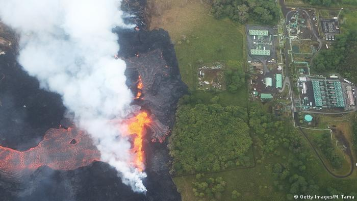Aeriel view shows active lava flow appraoching a geothermal power plant on Hawaii's Big Island.