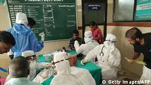 Medical personnel wearing protective suits check patients at the Medical College hospital in Kozhikode on May 21, 2018. - A deadly virus carried mainly by fruit bats has killed at least three people in southern India, sparking a statewide health alert May 21. Eight other deaths in the state of Kerala are being investigated for possible links to the Nipah virus, which has a 70 percent mortality rate. (Photo by - / AFP) (Photo credit should read -/AFP/Getty Images)