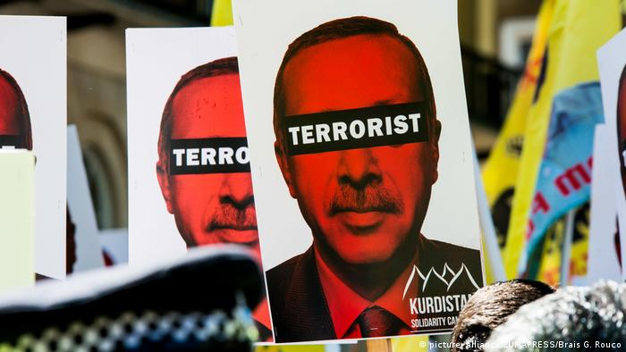 Kurdish protesters hold up a sign calling Erdogan a terrorist