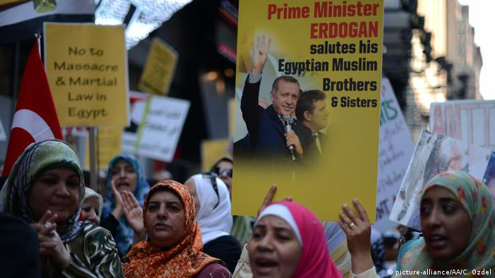 Protesters carry signs of Erdogan claiming to support the Muslim Brotherhood