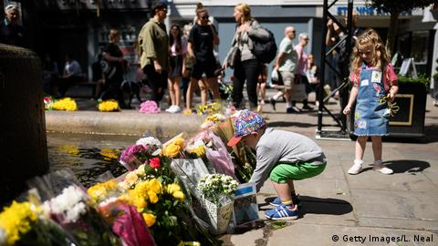 A young boy places a decorated stone among the floral tributes