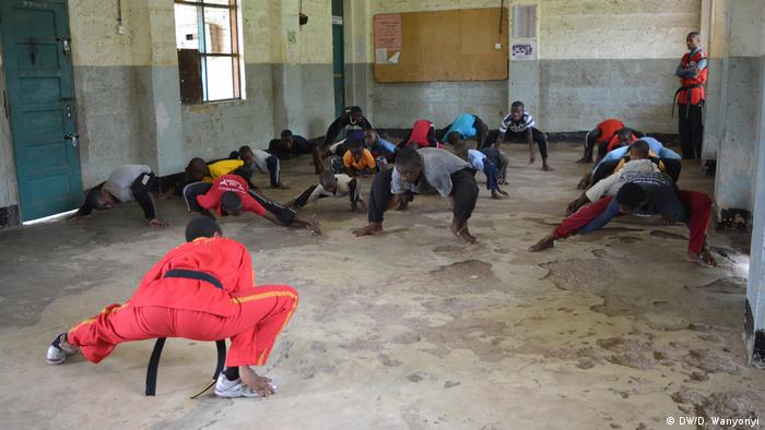 An instructor teaches children of all ages taekwondo in a town hall (DW/D. Wanyonyi)