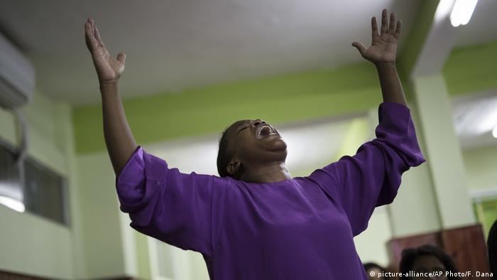 A member of the Assemblies of God Ministry of Restoration church reacts to the words of Pentecostal preacher Dione dos Santos in the Coreia shantytown
