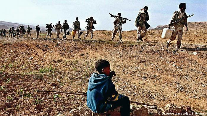 Soldiers from Eritrea march past a child on the to fight in 2000 (picture-alliance/dpa/S. Forrest)