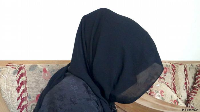 A woman in a black headscarf bows her head, concealing her face