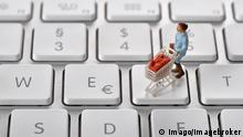 Figurine of woman with shopping trolley on keyboard (Imago/imagebroker)