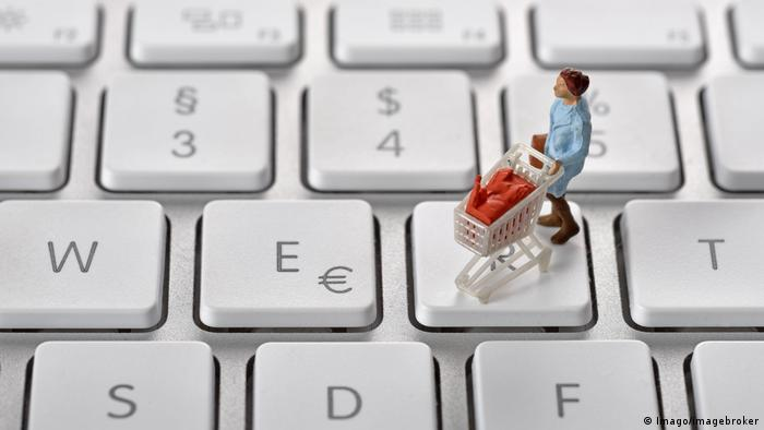 Figurine of woman with shopping trolley on keyboard