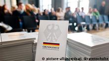 ARCHIV- Ein Grundgesetz der Bundesrepublik Deutschland liegt am 21.01.2015 bei einer Einbürgerungszeremonie im Neuen Rathaus in Hannover (Niedersachsen). Nach dem Brexit-Votum mehren sich die Anfragen von Briten zum Erwerb der deutschen Staatsbürgerschaft. Foto: Julian Stratenschulte/dpa (zu dpa Nach dem Brexit wird für Briten der deutsche Pass attraktiv vom 06.08.2016) +++(c) dpa - Bildfunk+++ | Verwendung weltweit