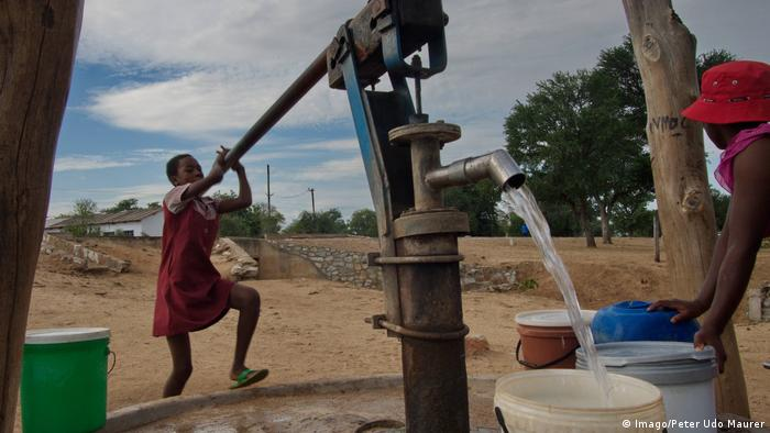 children pumping water in a village in Zimbabwe
