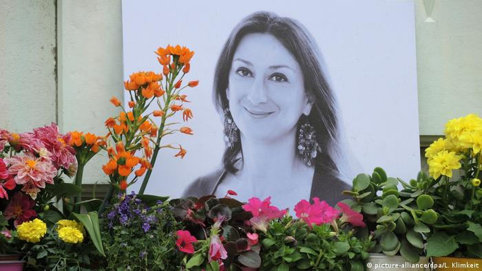 A memorial with flowers and a photo of Daphne Galizia