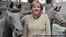 Bundeskanzlerin Angela Merkel (CDU) steht am Samstag (17.07.2010) in Qinling/ Xi'an (China) zwischen zwei Pferden der Terrakottaarmee. Die Bundeskanzlerin begeht am Samstag (17.07.) in Xi'an ihren 56. Geburtstag. Sie ist nach eigener Aussage im Jahr des Pferdes geboren. Merkel startete am 14.07. eine fünftägige Reise nach Russland, China und Kasachstan. Foto: Rainer Jensen dpa | Verwendung weltweit