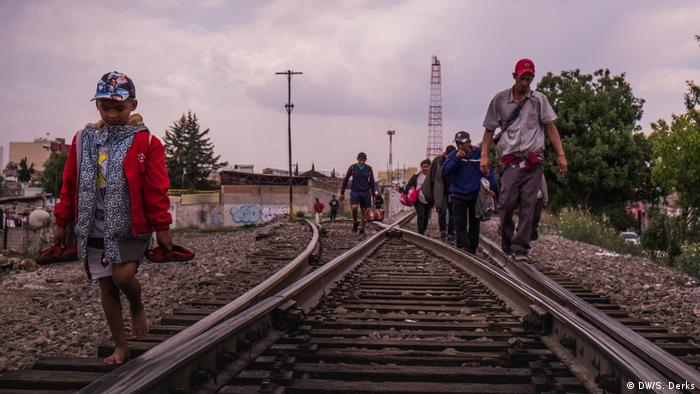 A group of refugees walking along train tracks (DW/S. Derks)