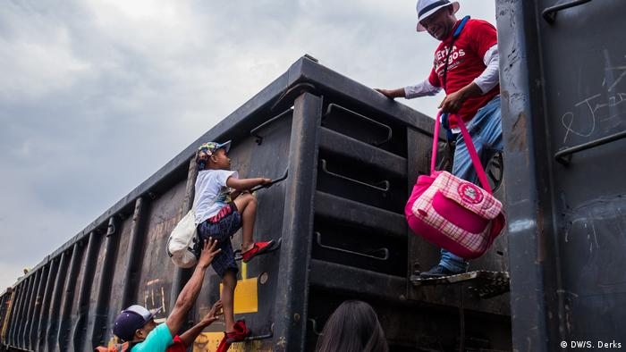 Refugees climbing onto a train (DW/S. Derks)
