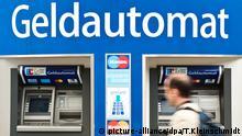 ARCHIV - ARCHIV - Ein Mann geht am 23.05.2011 in Berlin an Geldautomaten vorbei. (zu dpa:Der Geldautomat im Niedergangvom 15.04.2018) Foto: Tobias Kleinschmidt/dpa +++(c) dpa - Bildfunk+++ | Verwendung weltweit
