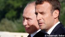 Russian President Vladimir Putin (L) speaks with French President Emmanuel Macron during a meeting in St. Petersburg, Russia May 24, 2018. REUTERS/Grigory Dukor